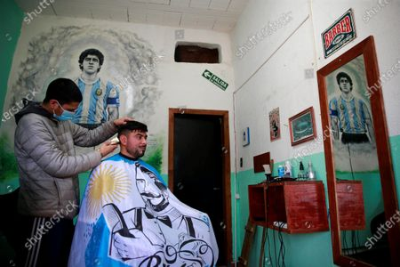 A view of a mural inside a hairdresser dedicated to late Diego A. Maradona in Lomas de Marilo neighborhood in the town of Bella Vista, Buenos Aires province, Argentina, 21 July 2021 (issued 23 July 2021). A few less than eight months after the death of Diego Maradona, residents of the neighborhood where he was buried told Efe that the area experiences a great 'revolution', both artistic and commercial, and that, still deceased, the soccer star continues to give them joy.