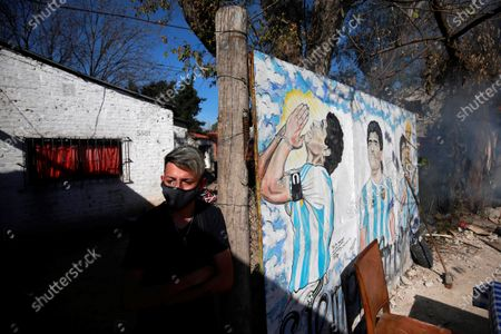 An inhabitant stands next to a mural dedicated to late Diego A. Maradona in Lomas de Marilo neighborhood in the town of Bella Vista, Buenos Aires province, Argentina, 21 July 2021 (issued 23 July 2021). A few less than eight months after the death of Diego Maradona, residents of the neighborhood where he was buried told Efe that the area experiences a great 'revolution', both artistic and commercial, and that, still deceased, the soccer star continues to give them joy.