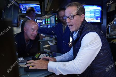 Specialists John O'Hara, left, and Glenn Carell work on the floor of the New York Stock Exchange, . Stocks rose in early trading on Wall Street Friday and put the major indexes on track for a strong finish in a week that opened with a stumble