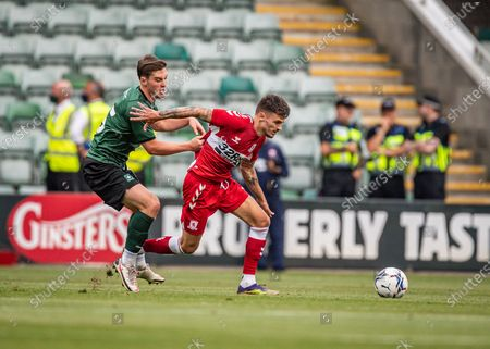 Plymouth Argyle midfielder Conor Grant (15) commits a foul and get hold of Middlesbrough Midfielder Sam Morsy (5) shirt  during the Pre-Season Friendly match between Plymouth Argyle and Middlesbrough at Home Park, Plymouth