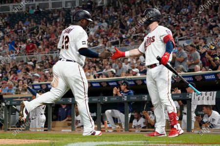 Minnesota Twins' Ryan Jeffers, right, congratulates Miguel Sano after Sano scored on a hit by Nick Gordon off Los Angeles Angels relief pitcher Steve Cishek during the sixth inning of a baseball game, in Minneapolis. The Twins won 5-4