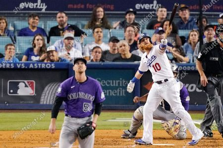 Los Angeles Dodgers' Justin Turner, right, heads to first as he hits a solo home run as Colorado Rockies starting pitcher Chi Chi Gonzalez watches during the third inning of a baseball game, in Los Angeles
