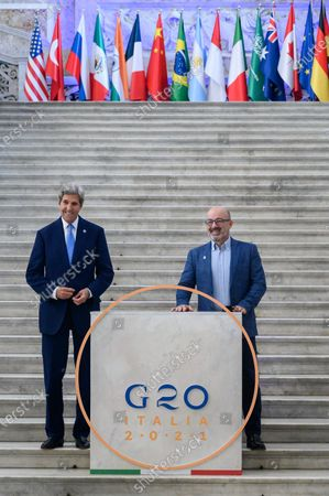Stock Picture of John Kerry (L), US Special Presidential Envoy for Climate, and Italian Minister for Ecological Transition Roberto Cingolani (R) pose for photographs behind the G20 logo.Italian Minister of the Ecological Transition Roberto Cingolani chaired the G20 Environment, Climate and Energy Joint Ministerial Meeting, on the second day in Naples, organized within the framework of the Italian Presidency of the G20. The meeting, held at the Royal Palace, had seen the participation of keynote speakers coming from the G20 countries and several international institutions and organizations.