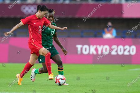China's Miao Siwen (9) dribbles the ball against Zambia's Racheal Kundananji (17) during a women's soccer match at the 2020 Summer Olympics, in Miyagi, Japan