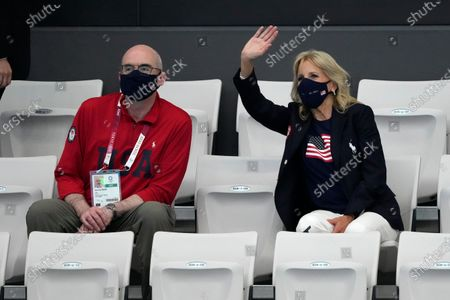 First Lady of the United States Jill Biden, right, waves as she sits next to Raymond Greene prior to the start of swimming competition at the 2020 Summer Olympics, in Tokyo