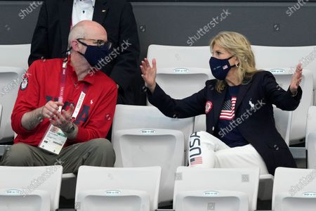 First Lady of the United States Jill Biden, right, gestures as she talks to Raymond Greene prior to the start of swimming competition at the 2020 Summer Olympics, in Tokyo, Japan