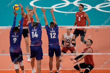 Stock Photo of United States' Matthew Anderson spikes a ball against France's Earvin Ngapeth, Nicolas le Goff and Stephen Boyer, during a men's volleyball preliminary round pool B match, at the 2020 Summer Olympics, in Tokyo, Japan
