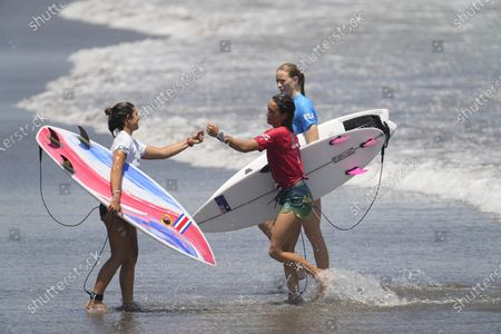 Costa Rica's Brisa Hennessy, left, gestures with Australia's Sally Fitzgibbons, and South Africa's Bianca Buitendag, during the first round of the women's surfing competition at the 2020 Summer Olympics, at Tsurigasaki beach in Ichinomiya, Japan
