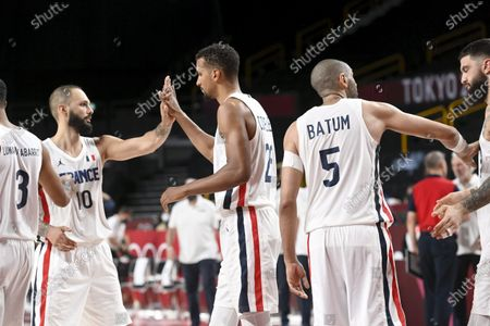 Evan Fournier (L) , Petr Cornelie and Nicolas Batum of France celebrate their 83-76 victory after the preliminary basketball game between France and the United States of America at the Tokyo Summer Olympic Games in the Saitama Super Arena in Saitama, on July 25, 2021.