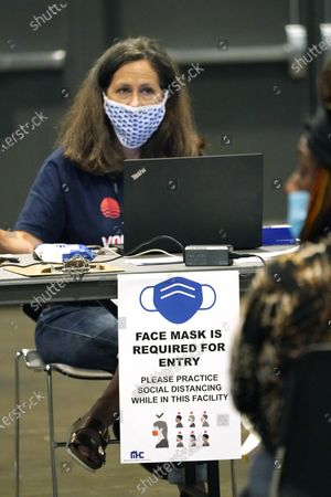Liz Brister, a volunteer from Entergy, a utility company, sits at her laptop behind a sign requiring all participants wear a face mask during a rental assistance fair for Jackson residents at the Mississippi Trademart in the state Fairgrounds, in Jackson, Miss. With the Delta virus variant cases increasing, officials required the applicants to be face masked during the two-day fair to apply for rental assistance through federal financial aid covering 15 months, and utility bill assistance for gas, electricity, water, sewer and trash removal