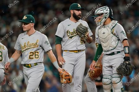 Oakland Athletics closing pitcher Lou Trivino, center, stands next to catcher Aramis Garcia, right, and Matt Chapman (26) after a mound conference during the ninth inning of a baseball game against the Seattle Mariners, in Seattle. Mariners' Jarred Kelenic scored a walk-off run on a wild pitch from Trivino and the Mariners won 5-4