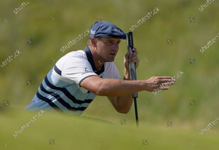 United States' Bryson DeChambeau gestures as he lines up his putt on the 2nd green during the third round of the British Open Golf Championship at Royal St George's golf course Sandwich, England. DeChambeau has tested positive for COVID-19 before leaving the United States for the Olympics and will miss the Tokyo Games. He'll be replaced by Patrick Reed