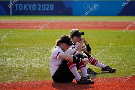 Canada's Erika Polidori, left, and Jennifer Gilbert, right, sit on the field after a loss to Japan in a softball game in Yokohama Baseball Stadium, at the 2020 Summer Olympics, in Yokohama, Japan