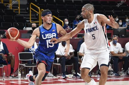 The United States' Devin Booker (L) looks to pass the ball as he defended by France's Nicolas Batum during a Men's Basketball game at the Tokyo 2020 Olympics, Sunday, July 25, 2021, in Tokyo, Japan.