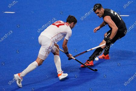 Spain's Vicenc Ruiz Torruella (21) and New Zealand's Nick Ross (7) battle for the ball during a men's field hockey match at the 2020 Summer Olympics, in Tokyo, Japan