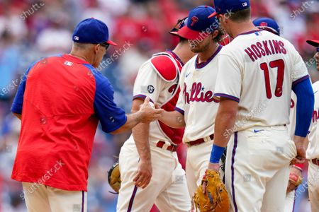 Stock Image of Philadelphia Phillies starting pitcher Aaron Nola, center, hands the ball off to manager Joe Girardi, left, as he is pulled during the ninth inning of a baseball game against the Atlanta Braves, in Philadelphia. The Phillies won 2-1