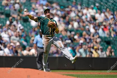 Stock Photo of Oakland Athletics third baseman Matt Chapman throws to first to get Seattle Mariners' Luis Torrens out on a ground out play during the second inning of a baseball game, in Seattle
