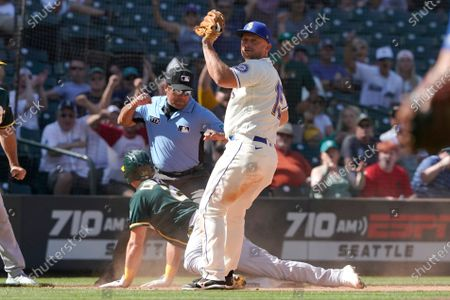 Seattle Mariners third baseman Kyle Seager, right, looks up after tagging out Oakland Athletics' Matt Chapman at third as third base umpire Nestor Ceja makes the call during the ninth inning of a baseball game as Champion tried to advance on a single hit by Mitch Moreland, in Seattle. The Mariners won 4-3