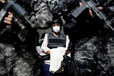 Erlinda Handal, former Deputy Minister of Health, is guarded by police agents as she arrives at a judicial headquarters, in San Salvador, El Salvador, 25 July 2021. The Attorney General's Office (FGR) of El Salvador presented this Sunday corruption charges against former President Salvador Sanchez Ceren (2014-2019) and nine other former officials before a court for allegedly receiving irregular payments in the administration of Mauricio Funes (2009- 2014).