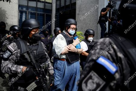 Carlos Caceres, former Minister of Finance, is guarded by police agents upon arriving at a judicial headquarters, in San Salvador, El Salvador, 25 July 2021. The Attorney General's Office (FGR) of El Salvador presented this Sunday corruption charges against former President Salvador Sanchez Ceren (2014-2019) and nine other former officials before a court for allegedly receiving irregular payments in the administration of Mauricio Funes (2009- 2014).