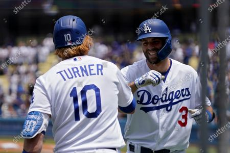 Los Angeles Dodgers' Chris Taylor, right, is congratulated by Justin Turner after hitting a solo home run during the first inning of a baseball game against the Colorado Rockies, in Los Angeles