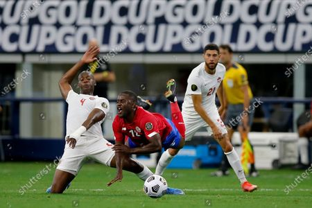 Canada defender Kamal Miller (4) sends Costa Rica forward Joel Campbell (12) flying while trying to strip the ball away as Canada's Jonathan Osorio (21) looks on in the first half of a 2021 CONCACAF Gold Cup quarterfinals soccer match, in Arlington, Texas