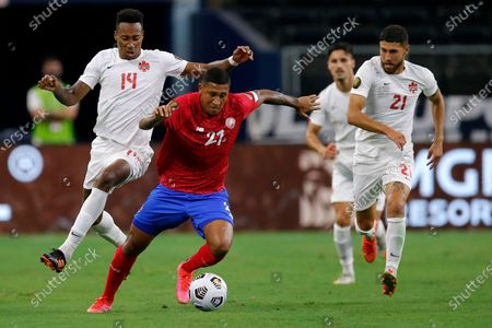 Canada defender Mark-anthony Kaye (14) and midfielder Jonathan Osorio (21) pressure as Costa Rica forward Jose Guillermo Ortiz (21) handles the ball in the second half of a 2021 CONCACAF Gold Cup quarterfinals soccer match, in Arlington, Texas