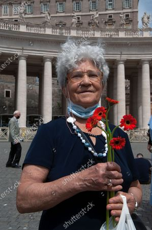 Faithful elders hold a gerbera flower symbolic of World Elders and Grandparents Day on St.Peter's Square for Pope Francis to deliver the Sunday Angelus prayer from the window of his study at the Vatican