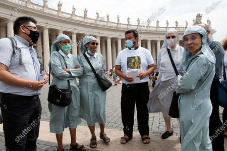 Nuns wiat on St.Peter's Square for Pope Francis to deliver the Sunday Angelus prayer from the window of his study at the Vatican