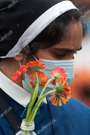 Nun and Faithful hold a gerbera flower symbolic of World Elders and Grandparents Day on St.Peter's Square for Pope Francis to deliver the Sunday Angelus prayer from the window of his study at the Vatican