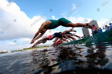 Henri Schoeman, front, of South Africa and Jonathan Brownlee, of Britain, jumps in to compete in the swim leg of the men's individual triathlon at the 2020 Summer Olympics, in Tokyo