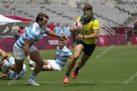 Argentina's Luciano Gonzalez goes in for the tackle as Australia's Josh Turner prepares to score a try in their men's rugby sevens match at the 2020 Summer Olympics, in Tokyo, Japan