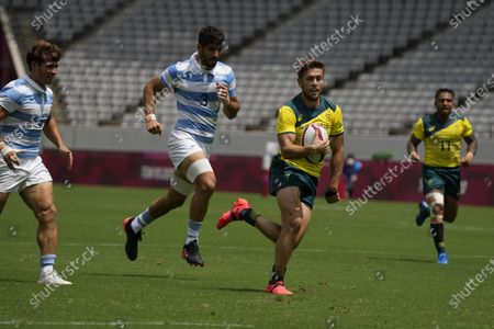 Australia's Josh Turner, center right, runs to score his second try pursued by Argentina's German Schulz, center left, and Rodrigo Etchart, left, in their men's rugby sevens match at the 2020 Summer Olympics, in Tokyo, Japan