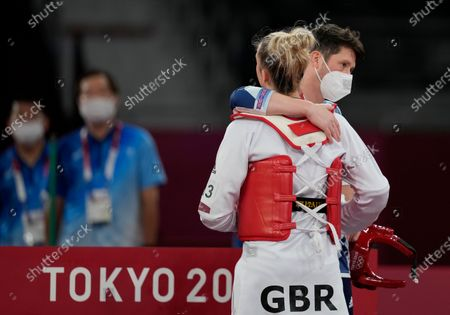 Britain's Lauren Williams, front, she embraced by coach Michael Harvey after was defeated by Croatia's Matea Jelic during a taekwondo women's 67kg match at the 2020 Summer Olympics, in Tokyo, Japan