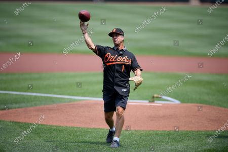 Baltimore Ravens head football coach John Harbaugh throws out the ceremonial first pitch using a football before a baseball game between the Baltimore Orioles and the Washington Nationals, in Baltimore