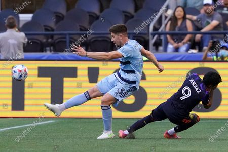 Sporting Kansas City defender Andreu Fontas (3) kicks the ball as Seattle Sounders forward Raul Ruidiaz (9) reacts to contact with Fontas during the first half of an MLS soccer match, in Seattle. Sporting Kansas City won 3-1
