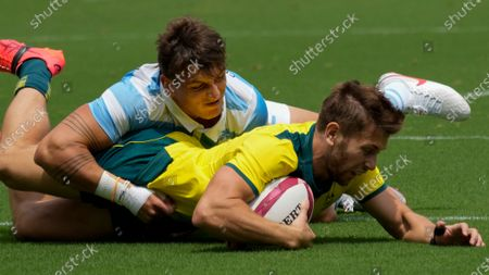Australia's Josh Turner scores a try as Argentina's Luciano Gonzalez defends in their men's rugby sevens match at the 2020 Summer Olympics, in Tokyo, Japan