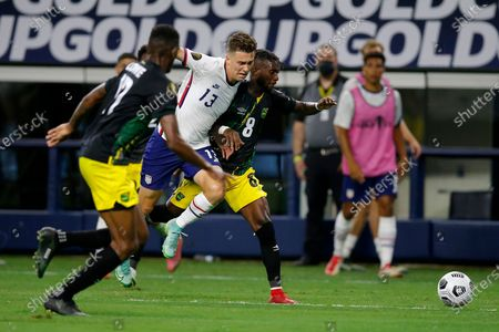 Jamaica defender Damion Lowe (17) and defender Oniel Fisher (8) attempt to keep control of the ball away from United States forward Matthew Hoppe (13) in the second half of a CONCACAF Gold Cup quarterfinals soccer match, in Arlington, Texas
