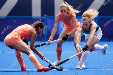 Ireland's Michelle Carey, right, battles for the ball against Netherlands' Maria Verschoor (11) and Laura Maria Nunnink (20) during a women's field hockey match at the 2020 Summer Olympics, in Tokyo, Japan