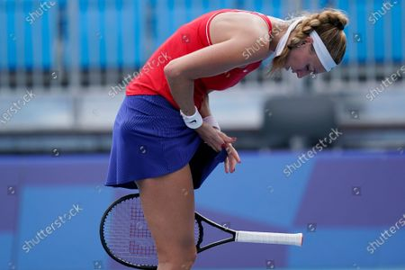 Petra Kvitova, of the Czech Republic, tries to wipe the sweat off her hands while playing Alison van Uytvanck, of Belgium, during the second round of the tennis competition at the 2020 Summer Olympics, in Tokyo, Japan