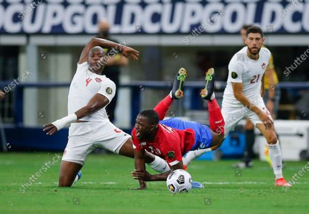 Canada defender Kamal Miller (4) trips Costa Rica forward Joel Campbell (12) during a CONCACAF Gold Cup Quarterfinals soccer match, in Arlington, Texas. Canada won 2-0