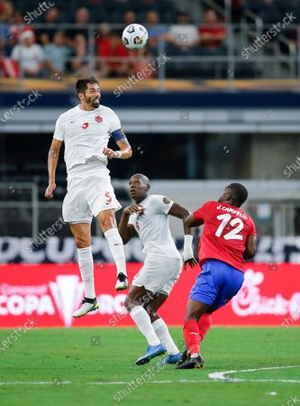 Canada defender Steven Vitoria (5) heads the ball as Costa Rica forward Joel Campbell (12) defends during a CONCACAF Gold Cup Quarterfinals soccer match, in Arlington, Texas. Canada won 2-0