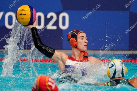 The Netherland's Nomi Stomphorst (6) looks for a teammate as she is defended by Australia's Rowie Webster (7) during a preliminary round women's water polo match at the 2020 Summer Olympics, in Tokyo, Japan