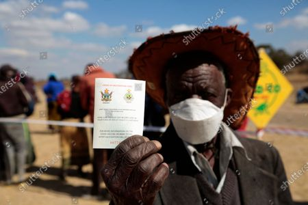 89 year old Mika Banda shows his covid -19 vaccination card during a vaccination drive against the covid -19 pandemic in Stapleford, Harare, Zimbabwe 26 July 2021. Many people are now being vaccinated as the country's covid-19 deaths rate surges with an average of 50 people dying daily this July alone.