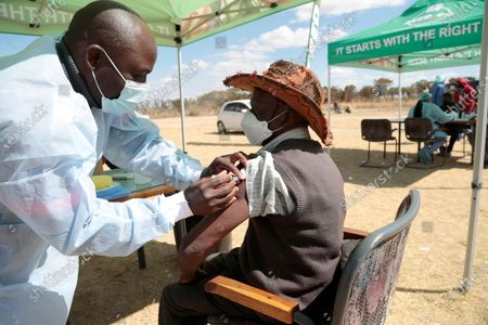 89 year old Mika Banda (R) gets vaccinated against the covid -19 pandemic in Stapleford, Harare, Zimbabwe 26 July 2021. Many people are now being vaccinated as the country's covid-19 deaths rate surges with an average of 50 people dying daily this July alone.