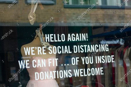 Covid-19 notices in the window of a Save The Children shop in Windsor