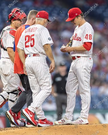 Philadelphia Phillies manager Joe Girardi (25) talks to starting pitcher Spencer Howard (48) before removing him from the mound after giving up four runs in the fourth inning of a baseball game against the Washington Nationals, in Philadelphia
