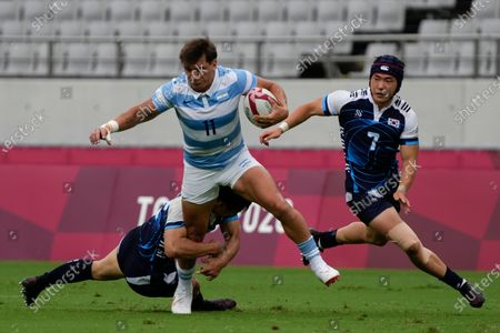 Argentina's Luciano Gonzalez tries to evade a tackle by South Korea's Kim Hyun-soo, as South Korea's Jang Jeong-min runs, in their men's rugby sevens match at the 2020 Summer Olympics, in Tokyo, Japan