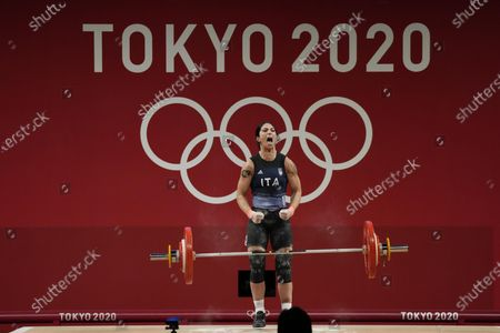 Maria Grazia Alemanno of Italy celebrates after a lift as she competes in the women's 59k weightlifting event, at the 2020 Summer Olympics, in Tokyo, Japan