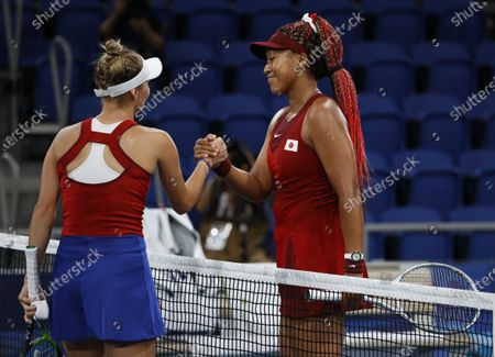 Naomi Osaka of Japan (R) shakes hands with  Marketa Vondrousova of the Czech Republic (L) after Vondrousova upset Osaka during the Women's Singles Third Round Tennis events of the Tokyo 2020 Olympic Games at the Ariake Coliseum in Tokyo, Japan, 27 July 2021.